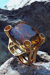 Citrine Crystal Ring - sitting upon a mountain side, with the crystal reflecting the mountainous terrain.